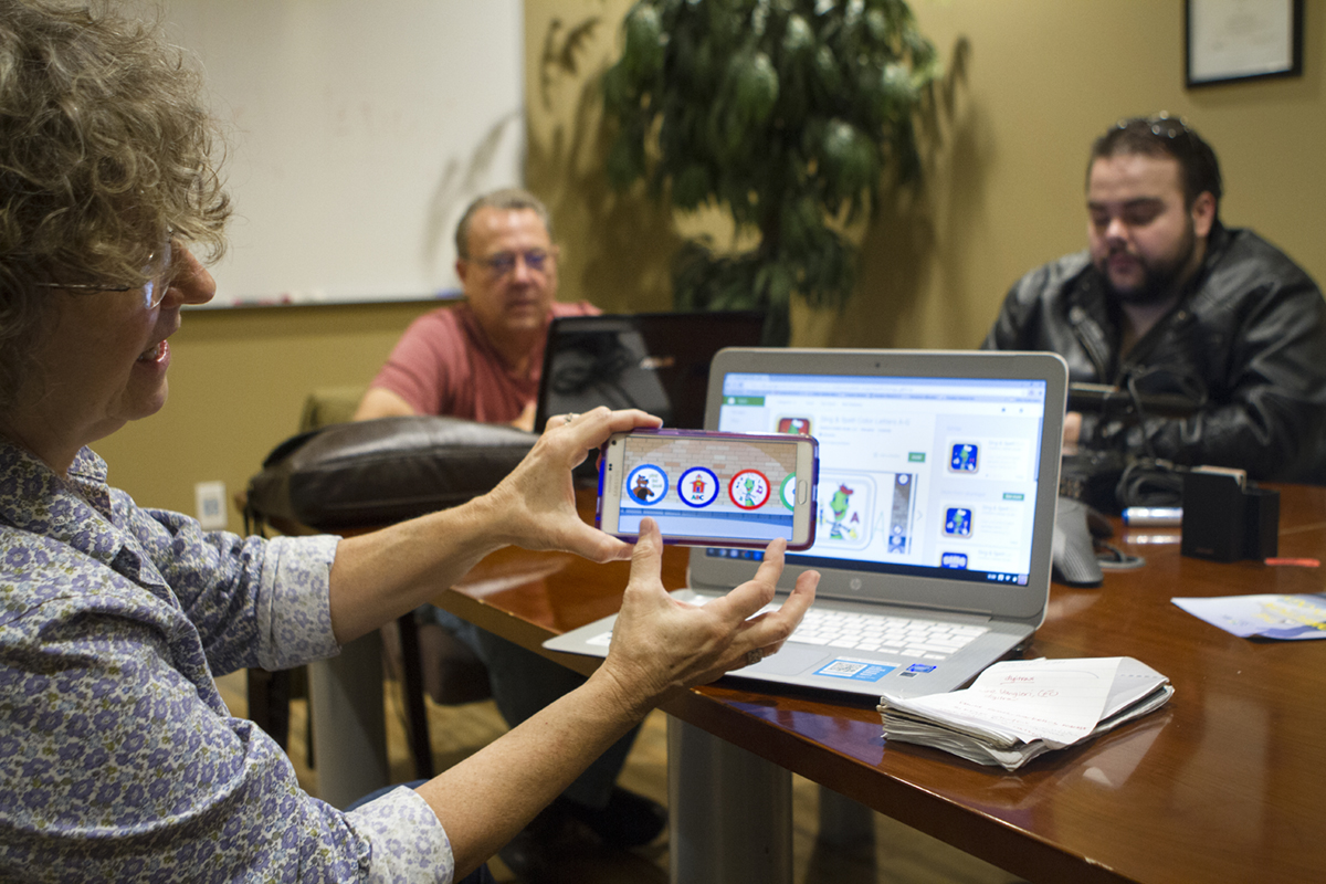 Cathy Vangieri, at left, demos a children's learning app with all original content and music developed and recently launched by Children's Media Studio, a division of Digitrax Entertainment.