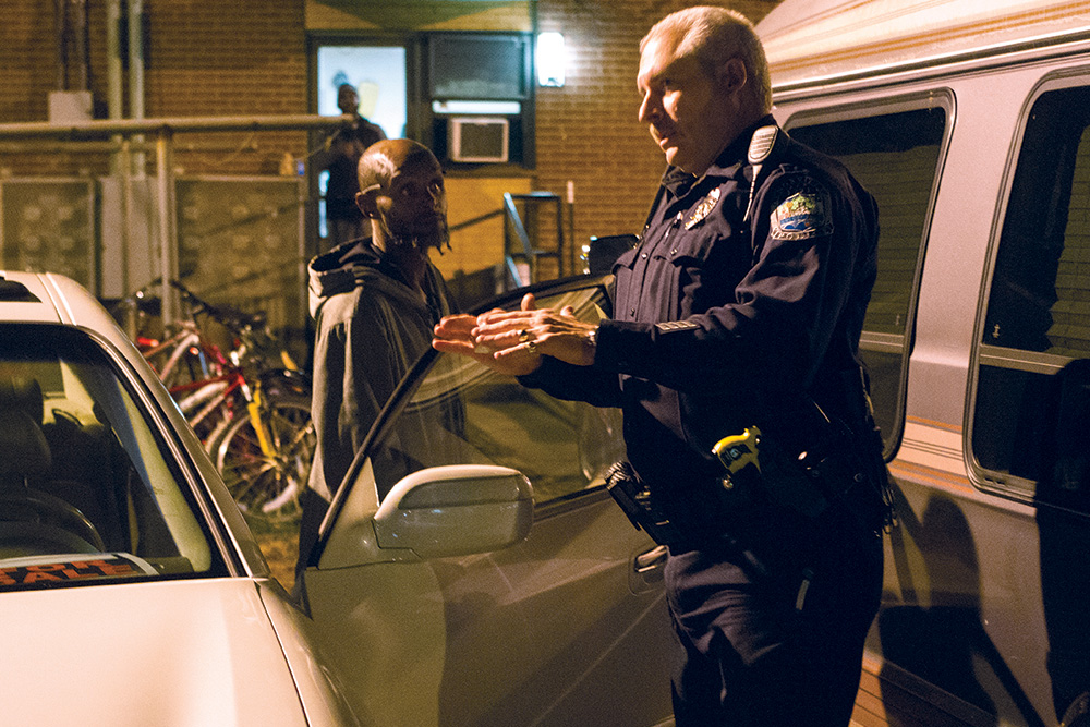 Knoxville police officer J.D. Hopkins talks with a group of people blasting music from a car stereo around midnight in Walter P. Taylor Homes in East Knoxville.