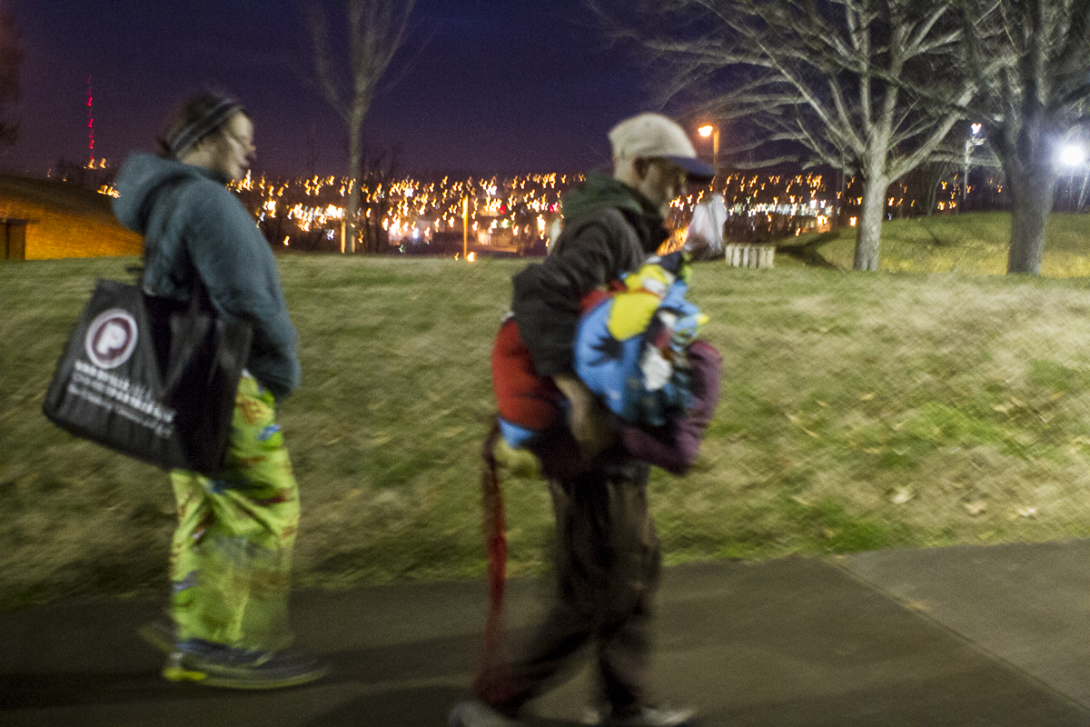 Drew Krikau and Stacy Holloway walk in the early morning hours after packing up tents and blanks. They spent the night on a wooded lot east of downtown Knoxville. Photo by Clay Duda.