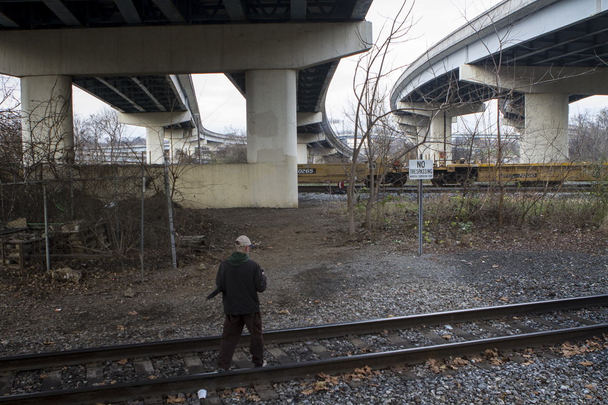 "Drew Krikau walks toward ""Tent City,"" as he calls it, under the Interstate 40 overpass in North Knoxville. Photo by Clay Duda."