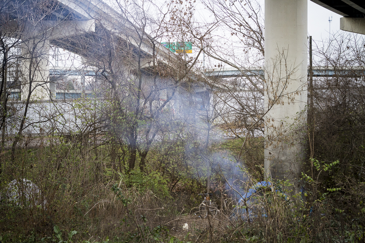 Smoke rises from a campfire under the Interstate 40 overpass in Knoxville. City officials and law enforcement plan to raze the encamp in the coming weeks. Photo by Clay Duda.