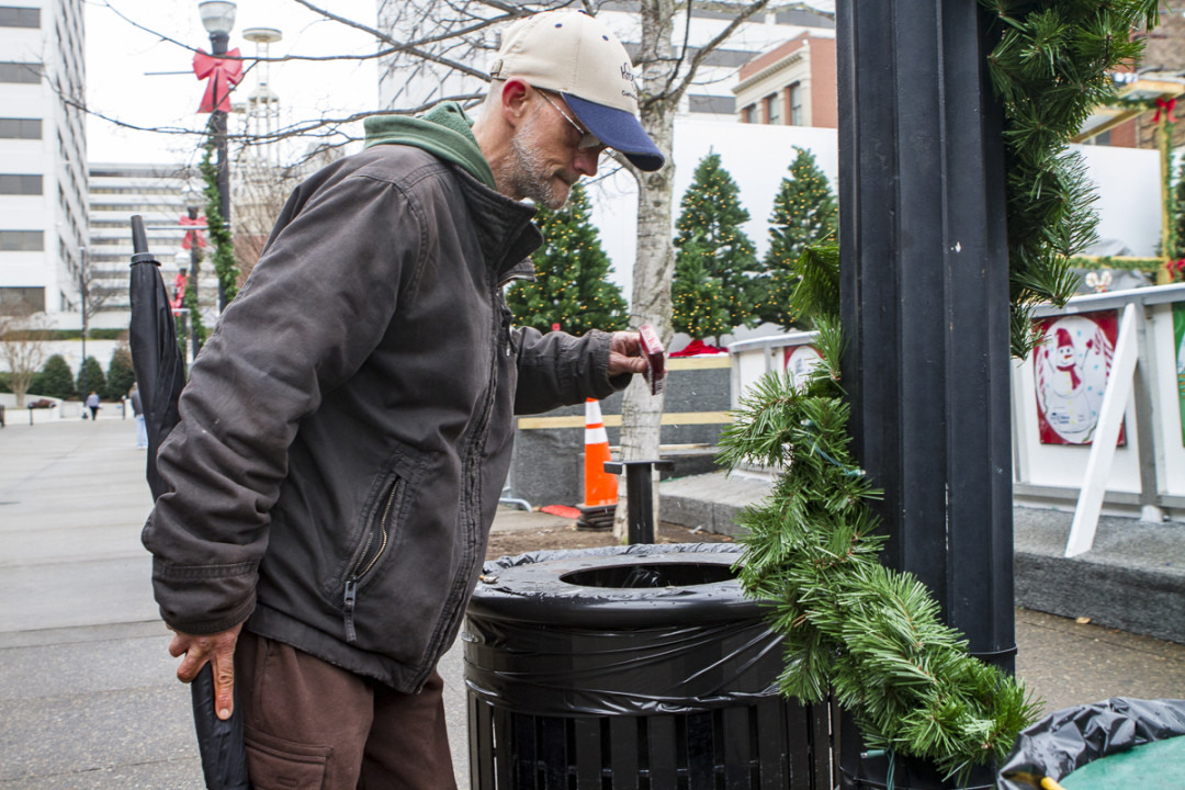 Drew Krikau skims trash bins in Knoxville's Market Square in search of anything good, a meal or, perhaps, a few spare cigarettes. Photo by Clay Duda.