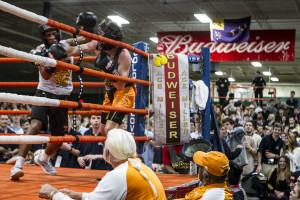Sam Dean of Sigma Alpha Epsilon, in orange shorts, and Major Morgan of Sigma Nu fight as judges look on during a qualifying round Thursday night. Neither boxer would advance on to the finals after two nights of preliminary bouts.
