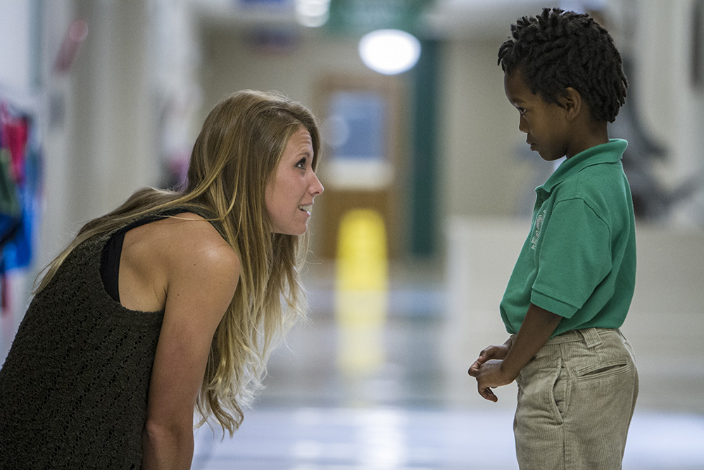 "Counselor Heidi Moles talks with a kindergartener in the halls at Emerald Academy during the second week of school. Each classroom is named after a university, as pictured above, and students are encouraged to speak in a confident ""college voice"" and raise their ""college hands"" in class."