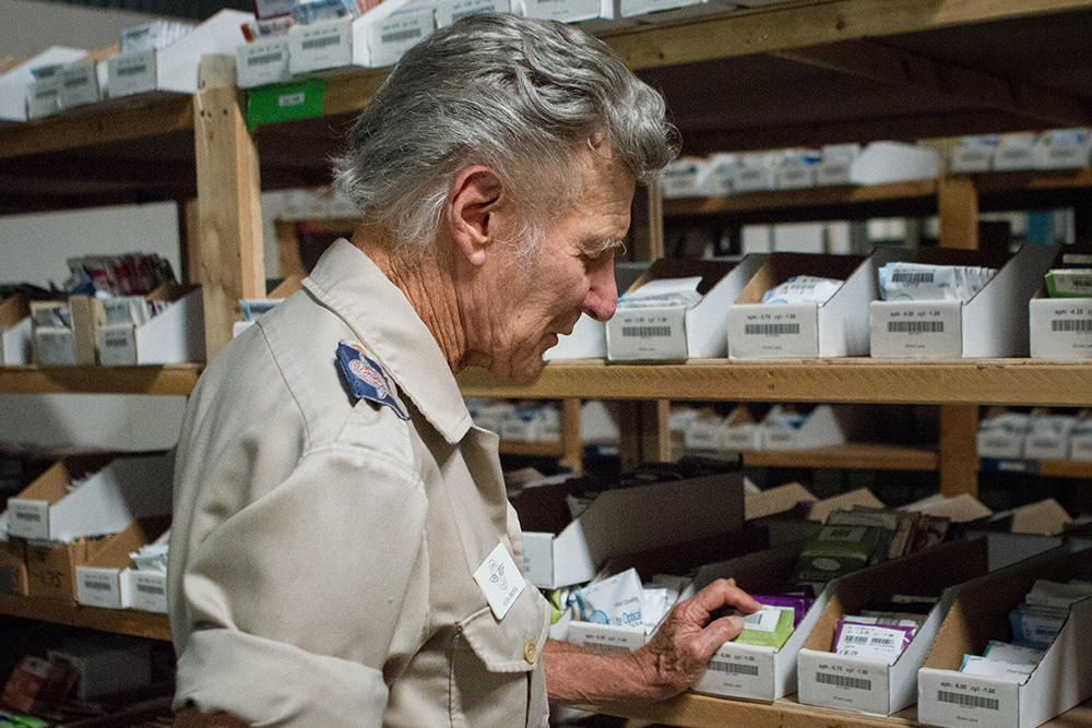 Remote Area Medical founder Stan Brock thumbs through an assortment of prescription lens at the nonprofit's headquarters in Rockford, Tenn.