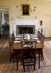 The family dining room at Blount Mansion—and its dining table set with replicas of period flatware and dishes—is overseen by a reverse glass painting of George Washington .