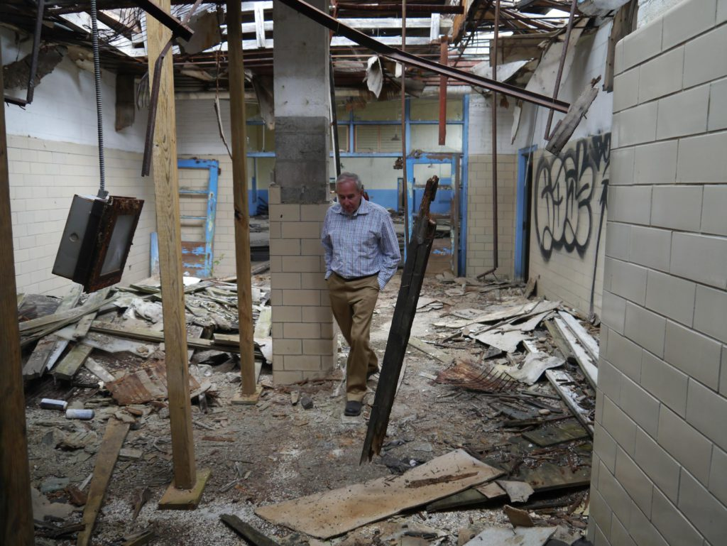 Monte Stanley walks through the ruins of South High School on Friday. He graduated from the school in 1965. The city announced the school's sale to a private developer for conversion to an assisted-living facility.