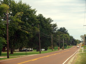 Utility poles and electric lines installed dangerously close to a typical rural roadway.